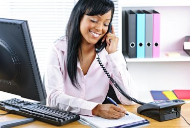 A lady answering the phone with confidence after attending a VoiceWorks course