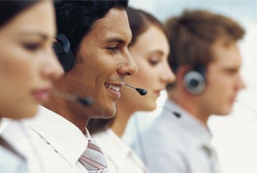 Multi-ethnic Customer Service Agents with headset on in a Call Centre