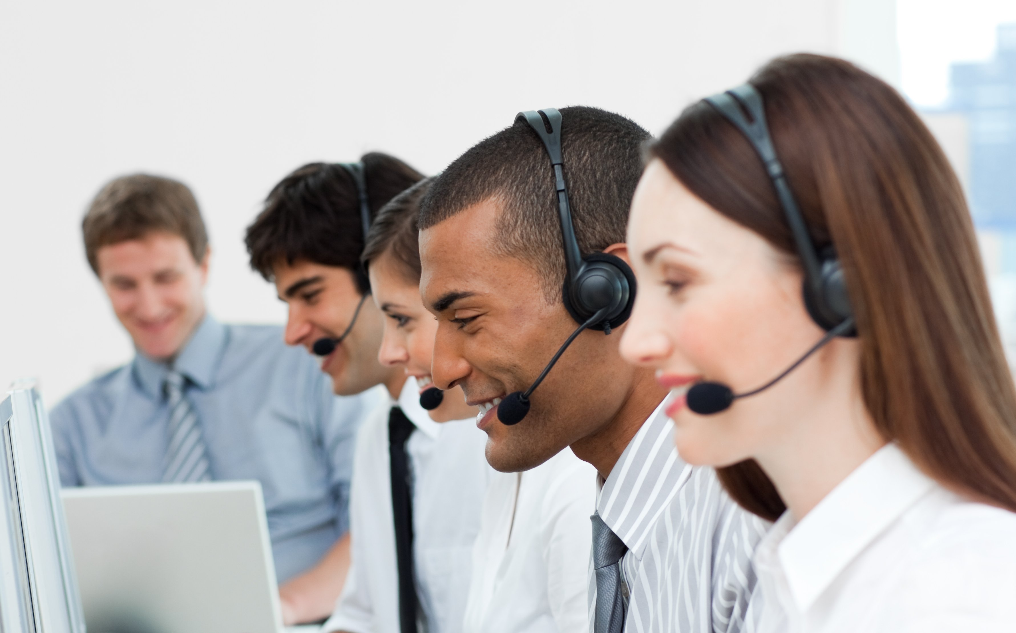 Multi-ethnic Customer Service Agents with headset on In A Call Center